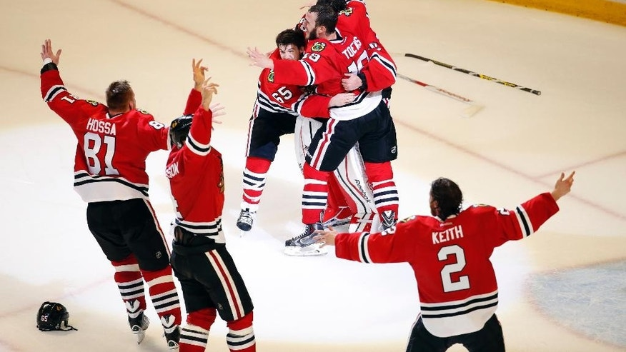 Members of the Chicago Blackhawks' celebrate after defeating the Tampa Bay Lightning in Game 6 of the NHL hockey Stanley Cup Final series on Monday, June 15, 2015, in Chicago. The Blackhawks defeated the Lightning 2-0 to win the series 4-2. (AP Photo/Charles Rex Arbogast)