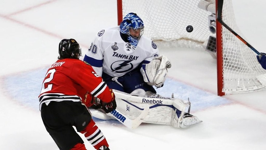 Chicago Blackhawks' Duncan Keith, left, scores past Tampa Bay Lightning goalie Ben Bishop during the second period in Game 6 of the NHL hockey Stanley Cup Final series on Monday, June 15, 2015, in Chicago. (AP Photo/Charles Rex Arbogast)