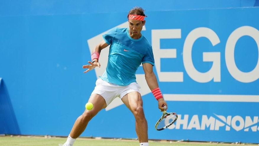 Spain's Rafael Nadal plays a return shot to Ukraine's Alexandr Dolgopolov during their men's singles tennis match at Queen's tennis championship in London, Tuesday June 16, 2015. (AP Photo/Tim Ireland)