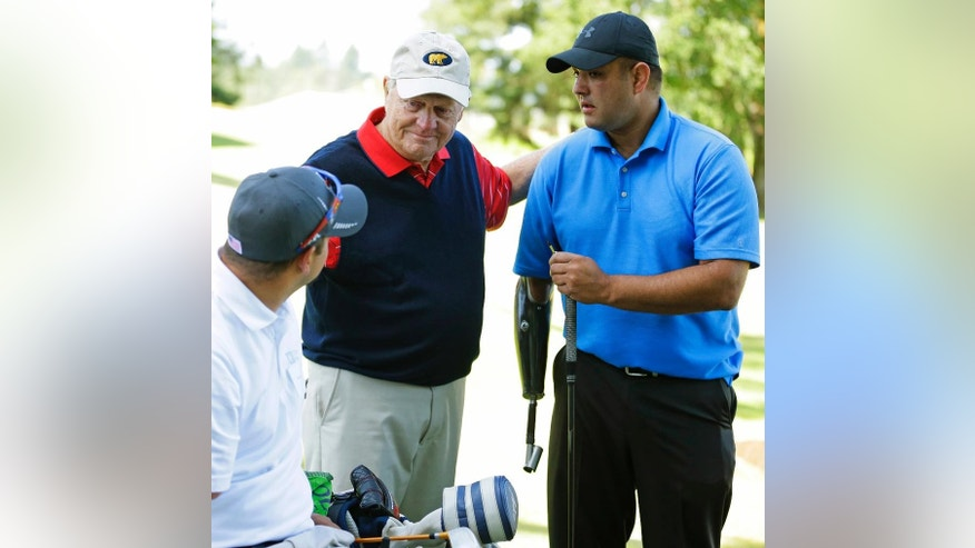 """Golfer Jack Nicklaus, center, talks with disabled golfers Leroy Petry, right, and Aaron Boyle, left, Tuesday, June 16, 2015 at American Lake Veterans Golf Course in Tacoma, Wash. Petry received the Medal of Honor in 2011 for for saving the lives of fellow soldiers when he picked up a grenade in Afghanistan, losing his hand in the process. Nicklaus was at the course to inspect the progress of the """"Nicklaus Nine,"""" nine new golf holes designed by Nicklaus as a donation to the course, which provides military veterans with both rehabilitation and recreation through golf. (AP Photo/Ted S. Warren)"""