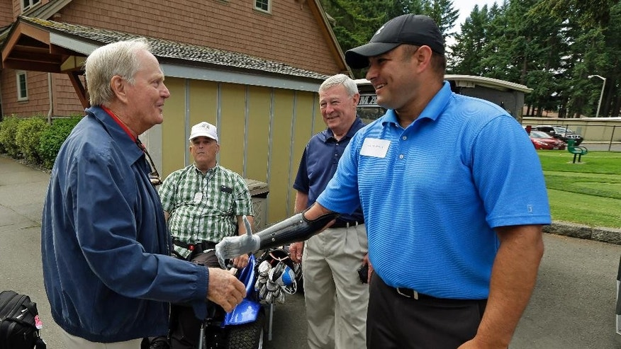 "Golfer Jack Nicklaus, left, shakes hands with Leroy Petry, right, Tuesday, June 16, 2015 at American Lake Veterans Golf Course in Tacoma, Wash. Petry, who golfs at the course, received the Medal of Honor in 2011 for for saving the lives of fellow soldiers when he picked up a grenade in Afghanistan, losing his hand in the process. Nicklaus was at the course to inspect the progress of the ""Nicklaus Nine,"" nine new golf holes designed by Nicklaus as a donation to the course, which provides military veterans with both rehabilitation and recreation through golf. (AP Photo/Ted S. Warren)"