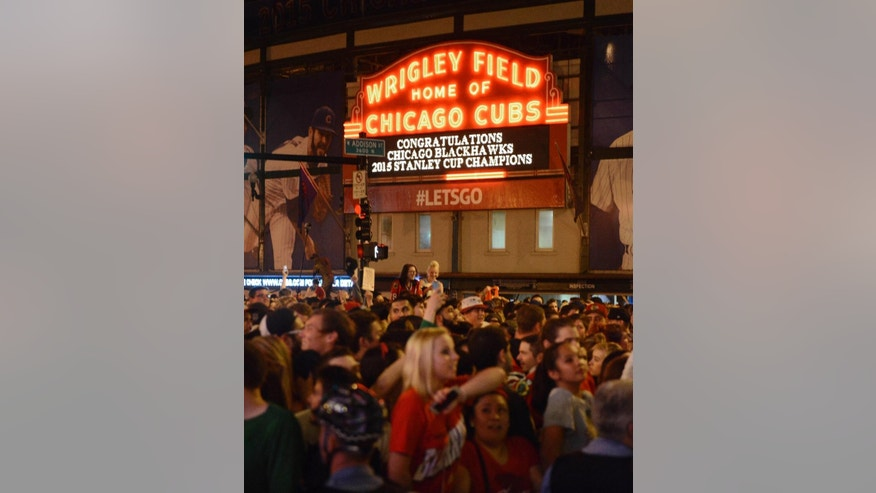 Chicago Blackhawks fans celebrate near Wrigley Field after the Blackhawks defeated the Tampa Bay Lightning to win the NHL hockey Stanley Cup, Monday, June 15, 2015, in Chicago. (AP Photo/Paul Beaty)