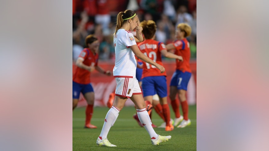 Spain's Virginia Torrecilla walks past as South Korea's Kim Sooyun (19) celebrates her goal with teammates during the second half of a FIFA Women's World Cup soccer match, Wednesday, June 17, 2015 in Ottawa, Ontario, Canada,  (Sean Kilpatrick/The Canadian Press via AP) MANDATORY CREDIT