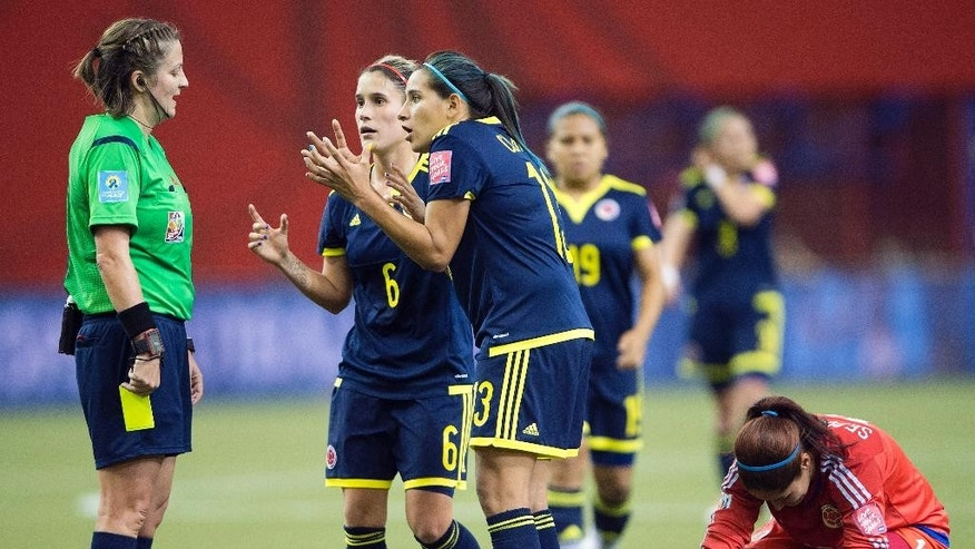 Colombia players Daniela Montoya(6) and Angela Clavijo (13) argue with the referee as she gives a yellow card to Colombia keeper Sandra Sepulveda, right, during the second half of a FIFA Women's World Cup soccer match, Wednesday, June 17, 2015, in Montreal, Canada. (Ryan Remiorz/The Canadian Press via AP) MANDATORY CREDIT