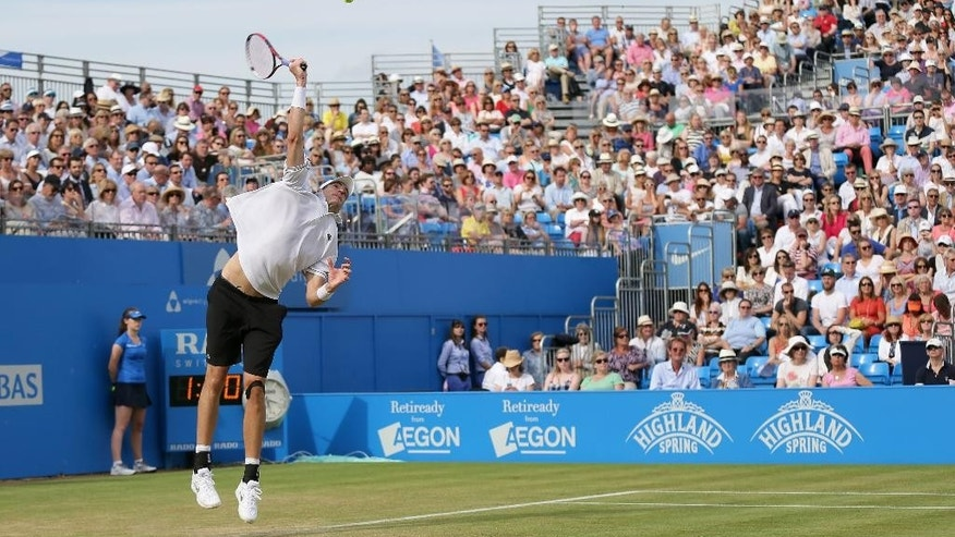 John Isner of the United States serves to Spain's Feliciano Lopez during their singles tennis match at the Queen's Championships in London, Thursday, June 18, 2015. (AP Photo/Tim Ireland)