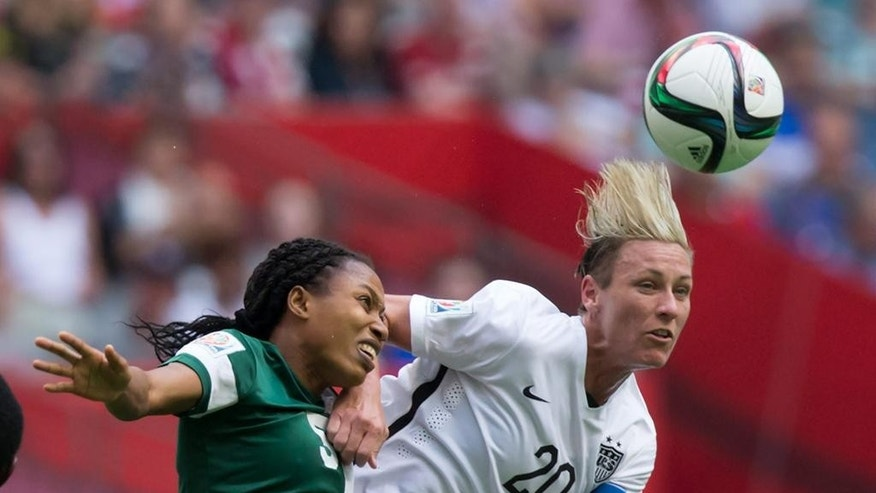 Nigeria's Onome Ebi, left, and United States' Abby Wambach vie for the ball during the second half of a FIFA Women's World Cup soccer game Tuesday, June 16, 2105, in Vancouver, British Columbia, Canada. (Darryl Dyck/The Canadian Press via AP)