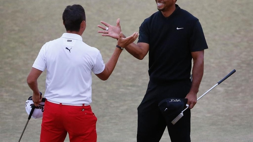 Tiger Woods, right, and Rickie Fowler shake hands after the first round of the U.S. Open golf tournament at Chambers Bay on Thursday, June 18, 2015 in University Place, Wash. (AP Photo/Lenny Ignelzi)