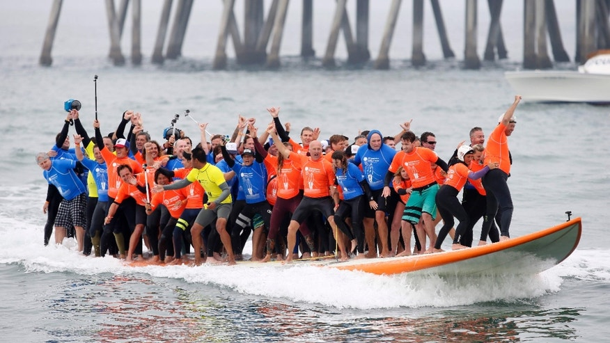 "June 20, 2015: Sixty-six surfers from around the world ride a custom built 42-foot, 1300 pound surfboard for 12 seconds to break the GUINNESS WORLD RECORDS® for ""Most People Riding a Surfboard at Once"""