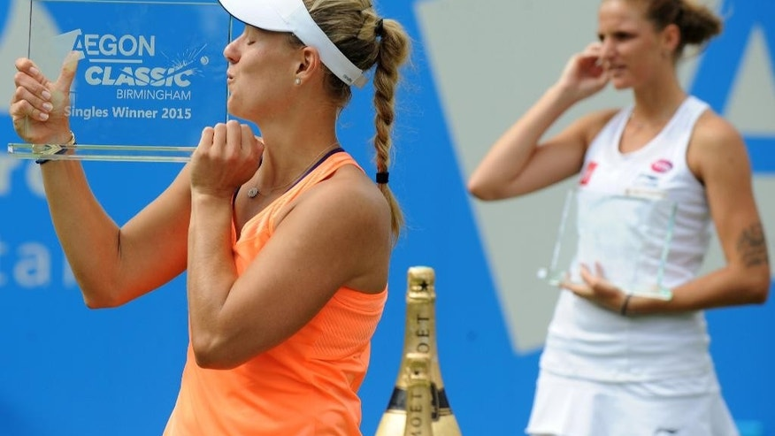 Germany's Angelique Kerber kisses the Aegon Trophy after beating Czech's Karolina Pliskova 6-7, 6-3, 7-6 during the Birmingham Classic Women's Singles Final at the Edgbaston Priory Club, Birmingham, England, Sunday, June 21, 2015. (AP Photo/Rui Vieira)
