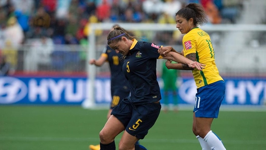 Australia's Laura Alleway, left, and Brazil's Christiane battle for the ball during first-half FIFA Women's World Cup soccer game action in Moncton, New Brunswick, Canada, Sunday, June 21, 2015. (Andrew Vaughan/The Canadian Press via AP) MANDATORY CREDIT