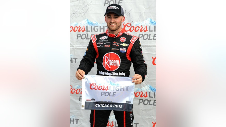 Austin Dillon holds the pole flag after qualifying first for the NASCAR Xfinity series auto race at Chicagoland Speedway, Saturday, June 20, 2015, in Joliet, Ill. (AP Photo/Nam Y. Huh)