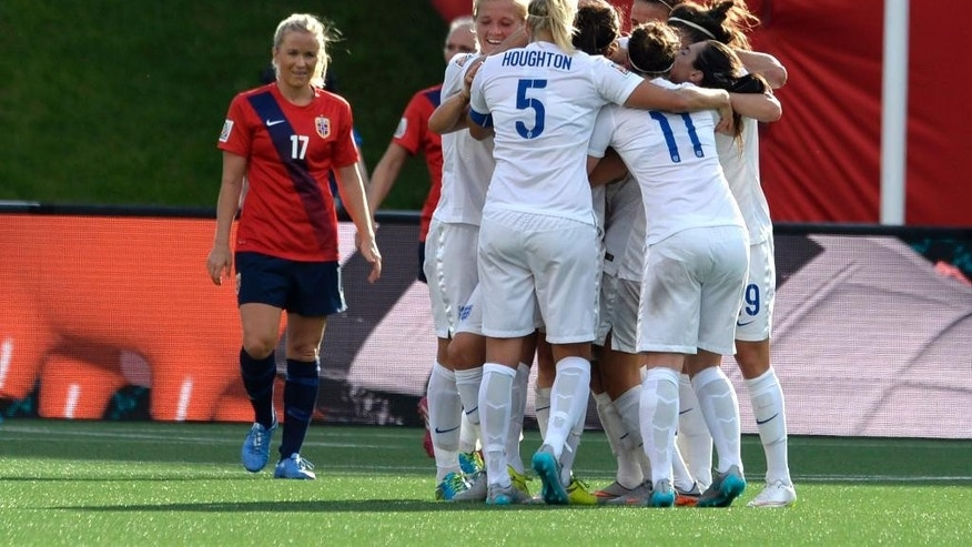 English players embrace following a goal by teammate Lucy Bronze as Norway's Lene Mykjaland (17) looks on in the second half of soccer action during the Round of 16 at the FIFA Women's World Cup Monday June 22, 2015, in Ottawa, Ontario, Canada. (Adrian Wyld/The Canadian Press via AP) MANDATORY CREDIT