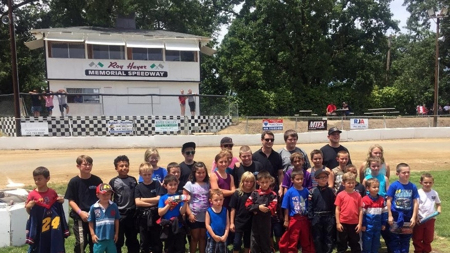 In this photo taken Saturday, June 20, 2015, NASCAR driver Jeff Gordon, rear third from right, poses with all the racers participating in the quarter-midget events at Roy Hayer Memorial Speedway in Rio Linda, Calif. Gordon began his career at the quarter-midget dirt track when he was 5 and the track was called Cracker Jack Track. (AP Photo/Jenna Fryer)