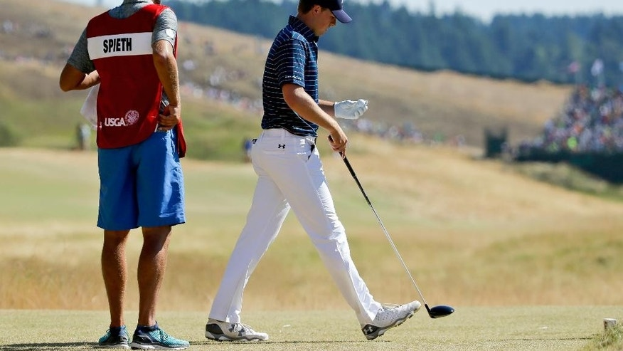 In this photo taken Sunday, June 21, 0215, Jordan Spieth, right and caddie Michael Greller stand on a tee during the final round of the U.S. Open golf tournament at Chambers Bay in University Place, Wash. Greller once hauled two golf bags around Chambers Bay in the mornings, then did it again with another in the afternoon, just to make a couple hundred bucks. His payday this week will be a whole lot better. (AP Photo/Ted S. Warren)