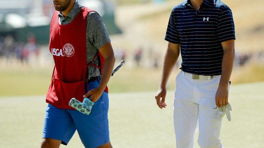 In this photo taken Sunday, June 21, 2015, Jordan Spieth, right and caddie Michael Greller walk down the fairway during the final round of the U.S. Open golf tournament at Chambers Bay in University Place, Wash. Greller once hauled two golf bags around Chambers Bay in the mornings, then did it again with another in the afternoon, just to make a couple hundred bucks. His payday this week will be a whole lot better. (AP Photo/Ted S. Warren)