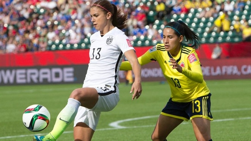 June 22, 2015: United States' Alex Morgan (13) kicks the ball in front ofColombia's Angela Clavijo (13) during first half FIFA Women's World Cup round of 16 action in Edmonton, Alberta, Canada.
