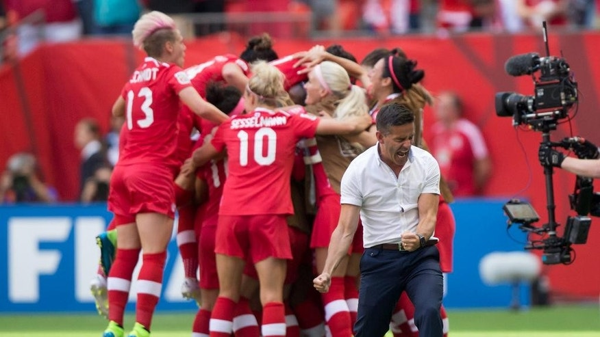 Canada coach John Herdman, right, celebrates as Josee Belanger, back, is mobbed by her teammates after scoring against Switzerland during the second half of the FIFA Women's World Cup round of 16 soccer action in Vancouver, British Columbia, Canada on Sunday June 21, 2015. (Darryl Dyck/The Canadian Press via AP)