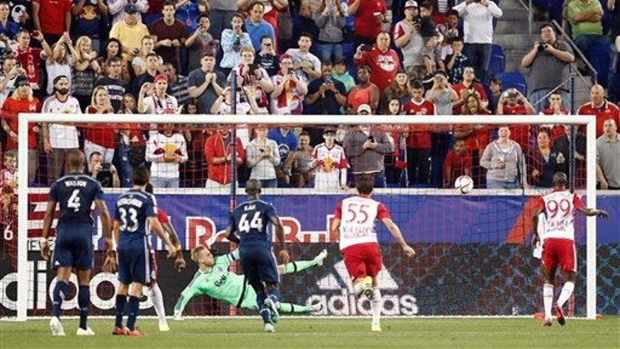 Vancouver Whitecaps FC goalkeeper David Ousted, center left, watches the ball after he deflected a penalty kick by New York Red Bulls forward Bradley Wright-Phillips, right, during the second half of an MLS soccer match, Saturday, June 20, 2015, in Harrison, N.J. Ousted denied Wright-Phillips on two penalty kicks and the Whitecaps won 2-1. (AP Photo/Julio Cortez)
