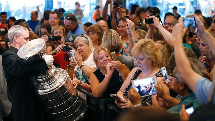 Fans take pictures of the Stanley Cup at the MGM Grand on Tuesday, June 23, 2015, in Las Vegas. If the NHL decides to gamble on an expansion franchise in the Nevada desert, most of the world's top hockey players are cautiously optimistic that the ice wouldn't melt. (AP Photo/John Locher)