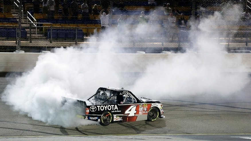 Erik Jones does a burnout after winning the NASCAR Truck Series auto race, Friday, June 19, 2015, at Iowa Speedway in Newton, Iowa. (AP Photo/Charlie Neibergall)