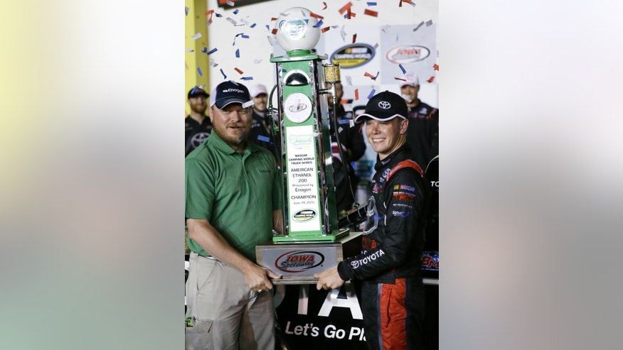 Erik Jones, right, receives the trophy after winning the NASCAR Truck Series auto race, Friday, June 19, 2015, at Iowa Speedway in Newton, Iowa. (AP Photo/Charlie Neibergall)