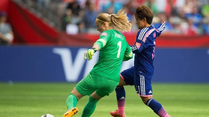 CORRECTS PHOTOGRAPHER - Netherlands goalkeeper Loes Geurts, left, is challenged by Japan's Shinobu Ohno during the first half of a round of 16 soccer match at the FIFA Women's World Cup, Tuesday, June 23, 2015, in Vancouver, British Columbia, Canada. (Darryl Dyck/The Canadian Press via AP)