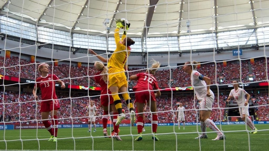 Canada goalkeeper Erin McLeod (1) makes a save as Switzerland's Caroline Abbe, second right, and Fabienne Humm, right, watch during the second half of the FIFA Women's World Cup round of 16 soccer action in Vancouver, British Columbia, Canada, Sunday, June 21, 2015. (Darryl Dyck/The Canadian Press via AP) MANDATORY CREDIT