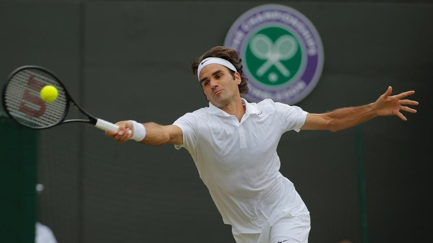 FILE - In this July 1, 2014, file photo, Roger Federer, of Switzerland, plays a return to Tommy Robredo in their men's singles match at the All England Lawn Tennis Championships at Wimbledon in London. (AP Photo/Pavel Golovkin, File)