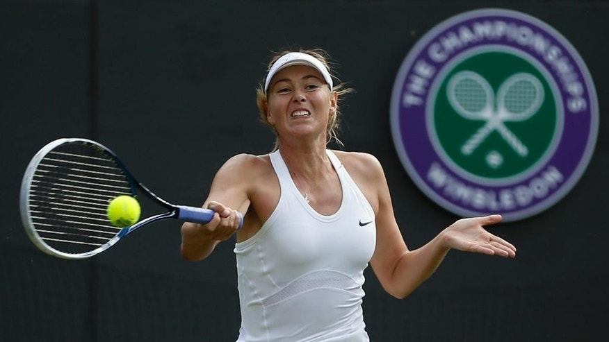 FILE - In this June 24, 2014, file photo, Maria Sharapova makes a return to Samantha Murray during a first round match at the All England Lawn Tennis Championships in Wimbledon, London. Sharapova won her first Grand Slam title as a 17-year-old at the All England Club, surprising Serena Williams in the final. (AP Photo/Pavel Golovkin, File)