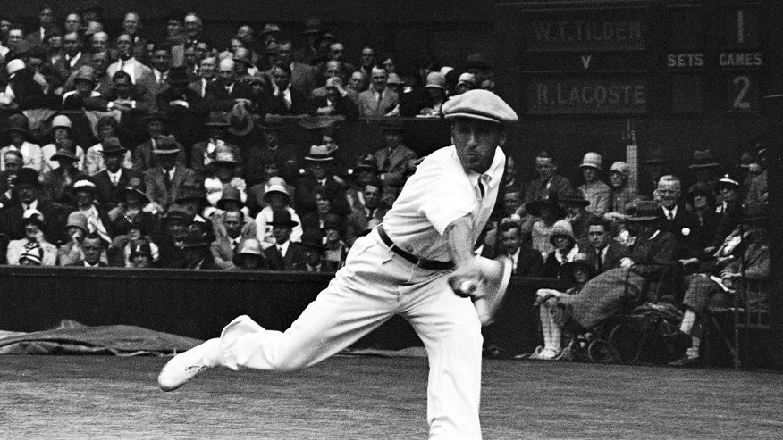 FILE - In this July 4, 1928 file photo, French tennis champion Rene Lacoste returns a shot,  during the men's singles semi-final match against American Bill Tilden, on the Centre Court at the All England Lawn Tennis Championships in Wimbledon, London. In the 1920s, French players dominated Wimbledon. In addition to Suzanne Lenglen winning five Wimbledon titles, three different Frenchmen triumphed, Rene Lacoste probably the most famous because of the clothing range he co-founded in 1933. Lacoste won two Wimbledons, as did his peers Jean Borotra and Henri Cochet, all between 1924 and 1929. (AP Photo, File)