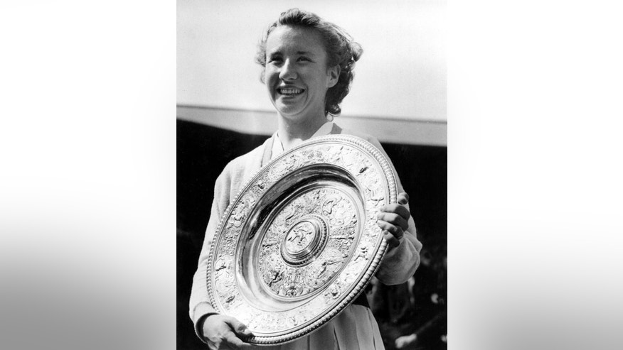 "FILE - In this July 5, 1952 file photo, Maureen ""Little Mo"" Connolly, of San Diego, Ca., smiles as she holds her trophy after winning the final in the women's singles at the All England Lawn Tennis Championships in Wimbledon, London.  In the early 1950s, Connolly dominated the world of tennis in much the same way as Helen Wills Moody did in the years before World War II. ""Little Mo"" won three straight Wimbledon titles from 1952-54, and in 1953 the Californian became the first woman to win the Grand Slam _ all four majors in the same year. The Associated Press named her ""Female Athlete of the Year"" for three years in a row in the early 1950s. Connolly died in 1969 at 34 after a long battle with cancer. (AP Photo, File)"