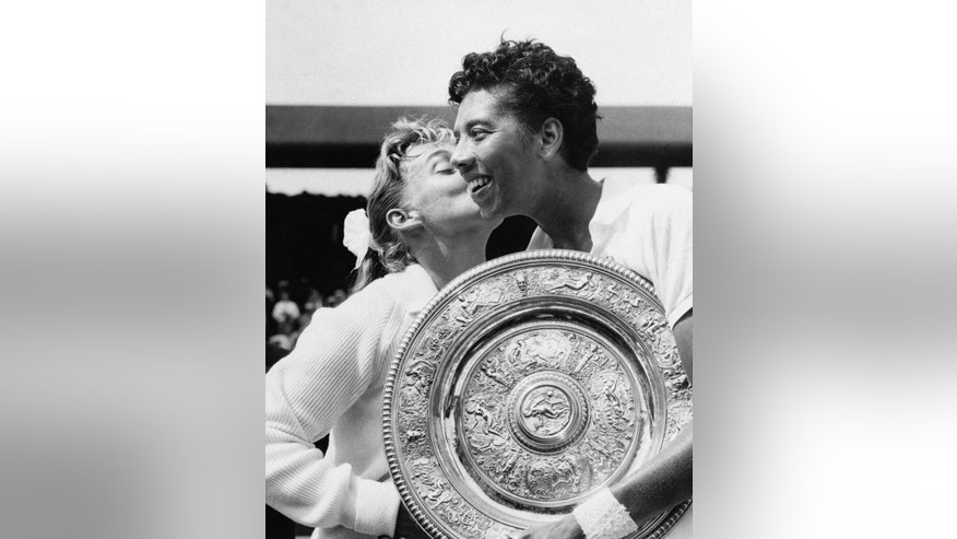 "FILE - In this July 6, 1957 file photo, Althea Gibson of New York city, holding the large gold plate presented to her as the winner of the Women's Singles Tennis title at the All England Lawn Tennis Championships in Wimbledon, London, is kissed by her opponent, Darlene Hard. Gibson became the first black player, male or female, to win Wimbledon when she defeated fellow American Hard in the final. She ended up with five Grand Slam singles titles, including two Wimbledon crowns, and was twice named The Associated Press' ""Female Athlete of the Year."" Her pioneering didn't end with tennis. In 1964, Gibson became the first black woman to play in the Ladies Professional Golf Association. (AP Photo, File)"
