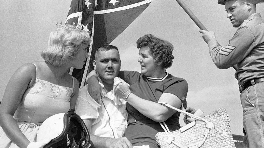 "FILE - In this Sept. 3, 1962, file photo, Junior Johnson, center, of Ronda, N.C., poses in Victory Lane with his sister, right, and Ginger Pointevint, Miss Sun Fun U.S.A., as man dressed as a Confederate soldier holds a Confederate flag, after Johnson won the 13th Annual Southern 500 auto race at the Darlington International Raceway in Darlington, S.C. NASCAR  backed South Carolina Gov. Nikki Haley's call this week to remove the Confederate flag from the Statehouse grounds in the wake of the Charleston church massacre. Though NASCAR now bars the use of the flag in any ""official capacity,"" they are as easy to find at NASCAR races as cutoff jeans, cowboy hats, and beer. (AP Photo/Perry Aycock, File)"