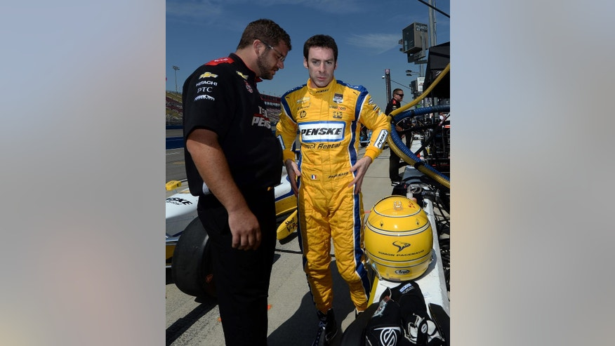 Simon Pagenaud, right, from France, speaks with a crew member following the opening practice session, Friday morning, June 26, 2015, for the IndyCar auto race at Auto Club Speedway in Fontana, Calif.  (AP Photo/Will Lester)