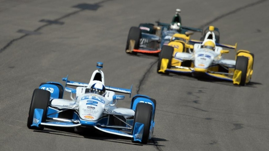Juan Pablo Montoya (2), from Colombia, leads teammate Simon Pagenaud (22), from France, towards turn one during the opening practice session, Friday morning, June 26, 2015, for the IndyCar auto race at Auto Club Speedway in Fontana, Calif.  (AP Photo/Will Lester)
