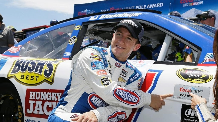 A.J. Allmendinger poses by his car after winning the pole position qualifying for the NASCAR Sprint Cup Series auto race Saturday, June 27, 2015, in Sonoma, Calif. (AP Photo/Eric Risberg)