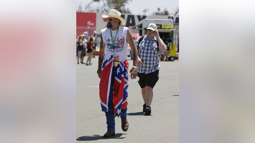 T.J. Woodward, left, of Sonoma, Calif., walks past the infield concession stand with a Confederate flag around his waist during practice for the NASCAR Sprint Cup Series auto race Friday, June 26, 2015, in Sonoma, Calif. (AP Photo/Eric Risberg)