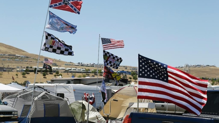 A number of flags, including a Confederate themed one,  fly atop RV's in a campground outside the track during practice for the NASCAR Sprint Cup Series auto race Friday, June 26, 2015, in Sonoma, Calif. (AP Photo/Eric Risberg)