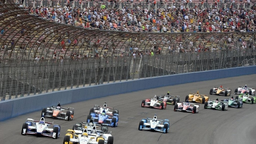 Simon Pagenaud (22), from France, leads the field toward Turn 1 on Saturday June 27, 2015, on the opening lap of the IndyCar auto race at Auto Club Speedway in Fontana, Calif. (AP Photo/Will Lester)