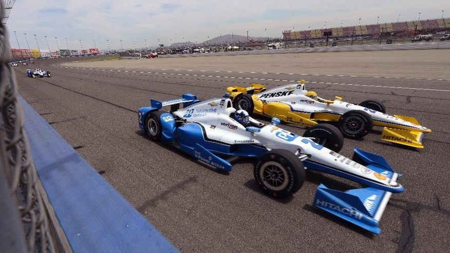 Juan Pablo Montoya (2), from Colombia, drives next to Simon Pagenaud, from France, Saturday, June 27, 2015, during the IndyCar auto race at Auto Club Speedway in Fontana, Calif. (AP Photo/Will Lester)