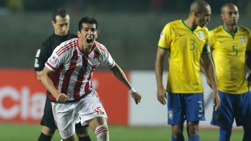 Paraguay's Victor Caceres celebrates after the penalty shootout during a Copa America quarterfinal soccer match at the Ester Roa Rebolledo Stadium in Concepcion, Chile, Saturday, June 27, 2015. Paraguay defeated Brazil 4-3 in a penalty shootout after a 1-1 draw on Saturday to advance to the semifinals of the Copa America. At right Brazil's Miranda and Fernandinho.(AP Photo/Natacha Pisarenko)