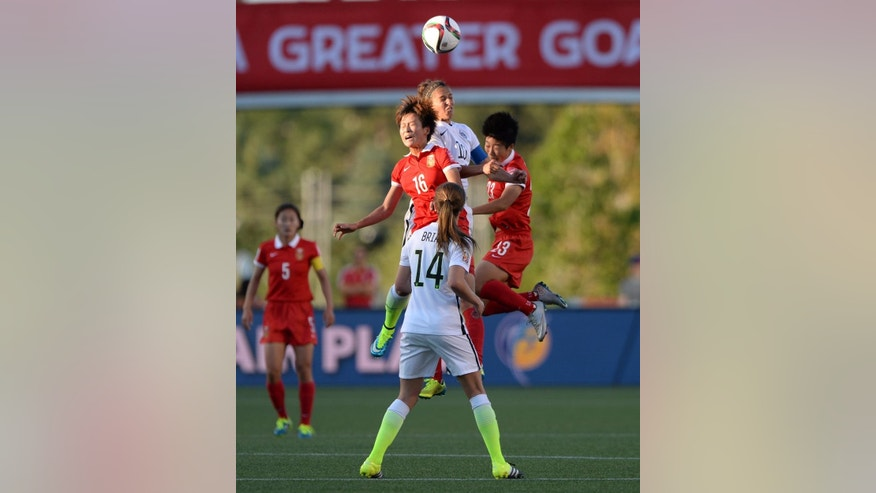 China's Lou Jiahui (16) and Ren Guixin (23) go up with United States' Carli Lloyd (10) for a header as United States' Morgan Brian (14) watches during the first half of a quarterfinal match in the FIFA Women's World Cup soccer tournament, Friday, June 26, 2015, in Ottawa, Ontario, Canada. (Sean Kilpatrick/The Canadian Press via AP)