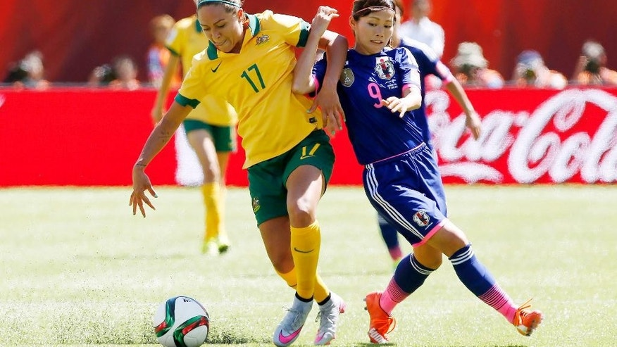 Australia's Kyah Simon, left, fights off a challenge by Japan's Nahomi Kawasumi during the second half of a FIFA Women's World Cup quarter-final soccer match in Edmonton, Alberta, Canada, Saturday, June 27, 2015. (Jeff McIntosh/The Canadian Press via AP) MANDATORY CREDIT