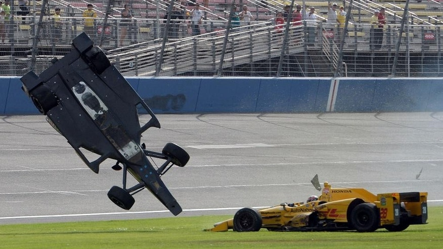 Ryan Briscoe flips through the infield grass next to Ryan Hunter-Reay on Saturday June 27, 2015 during the IndyCar auto race at Auto Club Speedway in Fontana, Calif. (AP Photo/Will Lester)