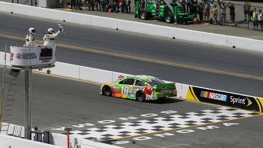 Kyle Busch crosses the finish line to win the NASCAR Sprint Cup Series auto race Sunday, June 28, 2015, in Sonoma, Calif. (AP Photo/Eric Risberg)