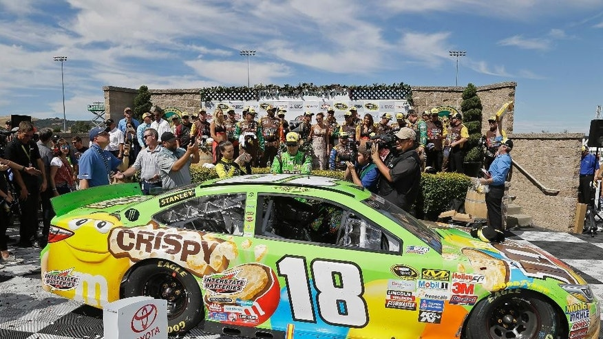 Kyle Busch places a winner's sticker on his car after winning the NASCAR Sprint Cup Series auto race Sunday, June 28, 2015, in Sonoma, Calif. (AP Photo/Eric Risberg)