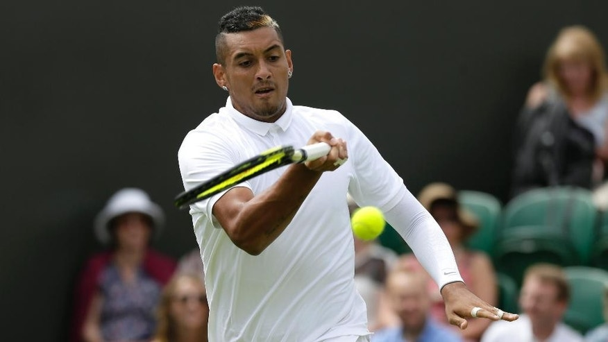 Nick Kyrgios of Australia returns a ball to Diego Schwartzman of Argentina during the men's singles first round match at the All England Lawn Tennis Championships in Wimbledon, London, Monday June 29, 2015. (AP Photo/Tim Ireland)