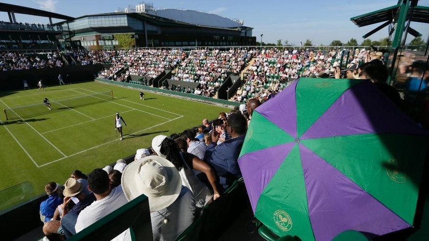 People shelter from the sun under an umbrella during the women's singles first round match between Venus Williams of the United States and Madison Brengle of the United States at the All England Lawn Tennis Championships in Wimbledon, London, Monday June 29, 2015. (AP Photo/Tim Ireland)