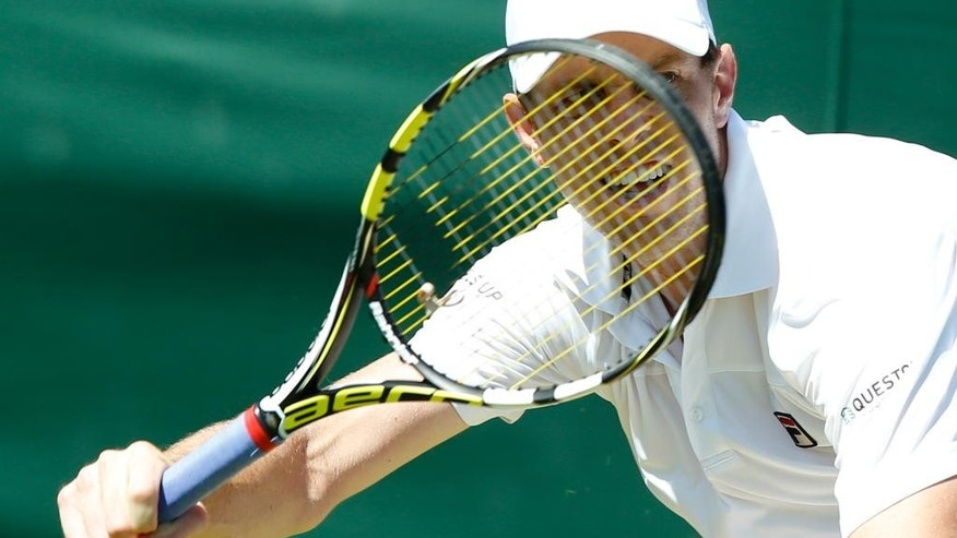 Sam Querrey of the United States returns a ball to Igor Sijsling of the Netherlands during the men's singles first round match at the All England Lawn Tennis Championships in Wimbledon, London, Tuesday June 30, 2015. (AP Photo/Alastair Grant)