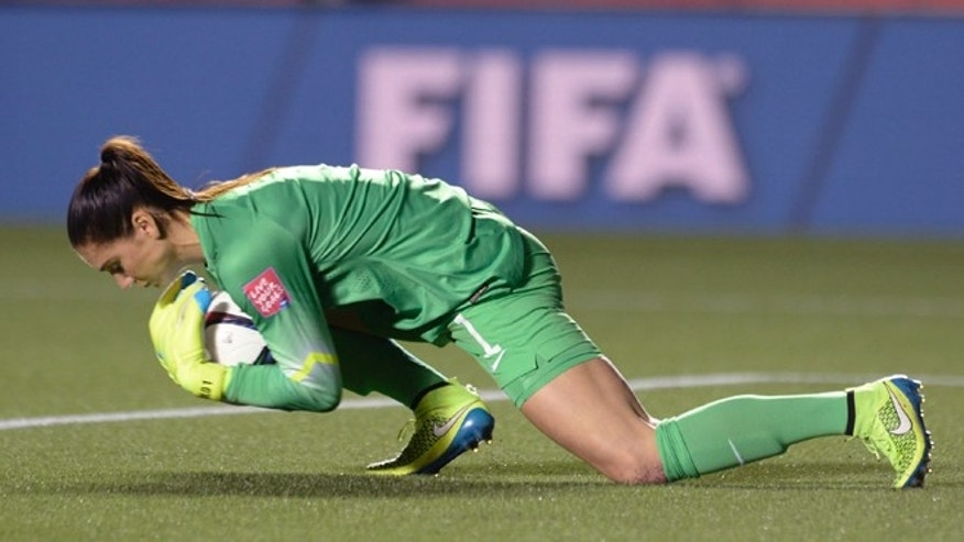 U.S. keeper Hope Solo makes a save against China in the World Cup soccer tournament, Friday, June 26, 2015, in Ottawa.